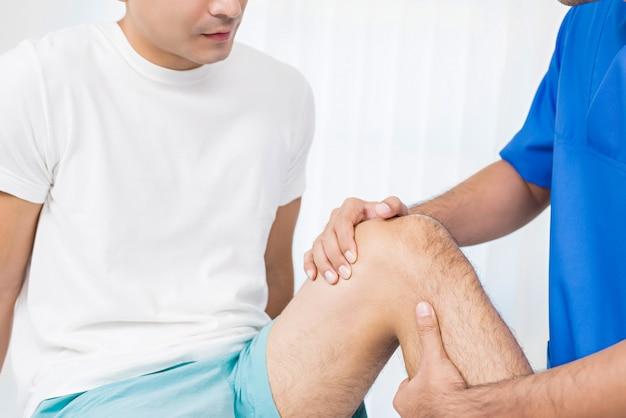Fisioterapeuta que trata joelho ferido de paciente do sexo masculino no hospital