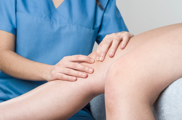 Fisioterapeuta, quiroprático fazendo mobilização patelar, dor no joelho
