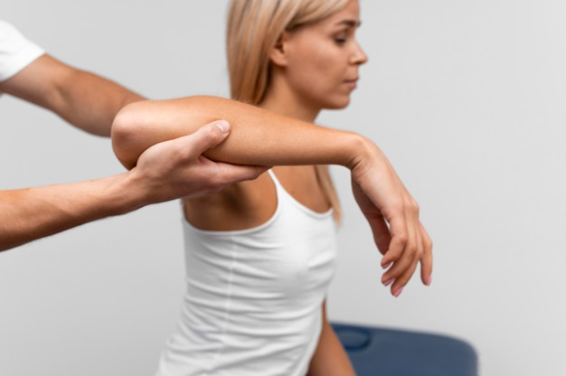 Fisioterapeuta realizando exercícios de ombro com paciente do sexo feminino