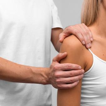 Fisioterapeuta realizando exercícios de ombro em paciente do sexo feminino