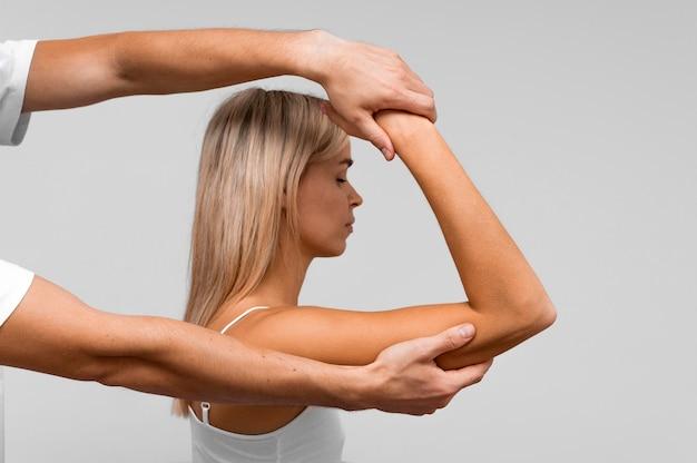 Fisioterapeuta realizando exercícios na mulher