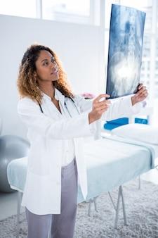 Fisioterapeuta, segurando o raio-x da coluna do paciente