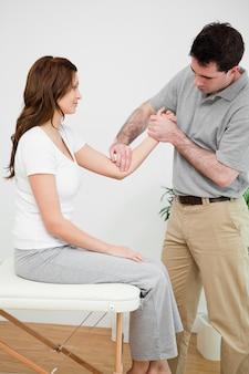 Fisioterapeuta séria tocando o cotovelo de uma mulher em um quarto