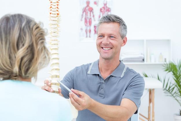 Fisioterapeuta sorridente que mostra o modelo da coluna para o paciente