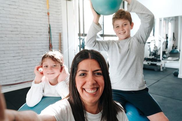Fisioterapeuta tirando uma selfie com as crianças que atende durante sua consulta, pois estão feridas