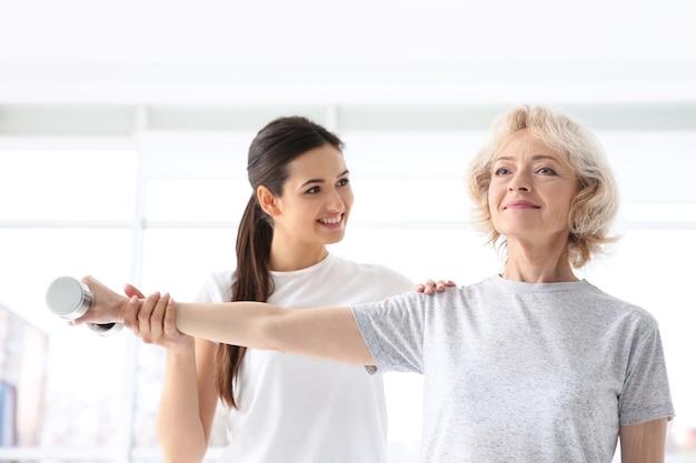 Fisioterapeuta trabalhando com paciente idoso em clínica moderna