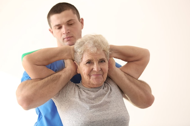 Fisioterapeuta trabalhando com paciente idoso na clínica