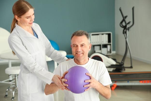 Fisioterapeuta trabalhando com paciente maduro em centro de reabilitação