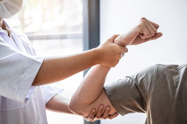 Fisioterapeuta trabalhando examinando o tratamento de lesões no braço de paciente atleta do sexo masculino, alongamento e exercícios, fazendo a terapia de reabilitação da dor na clínica.