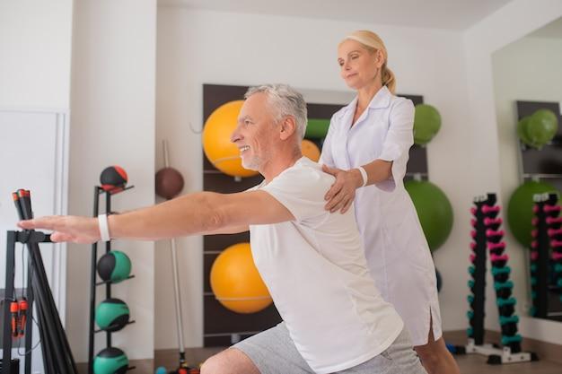 Fisioterapeuta usando jaleco trabalhando com um paciente
