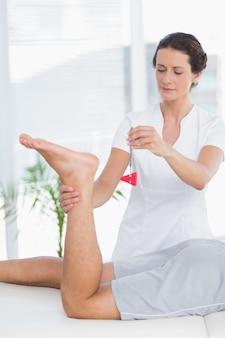Fisioterapeuta usando martelo reflexo