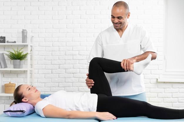 Fisioterapeuta verificando a flexibilidade das pernas da mulher