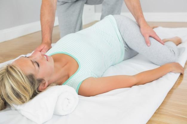 Fisioterapeuta, verificando os quadris de pacientes em uma esteira no chão