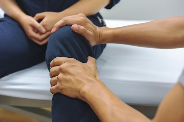 Fisioterapeutas estão verificando lesões no joelho para o paciente. conceito médico e de saúde