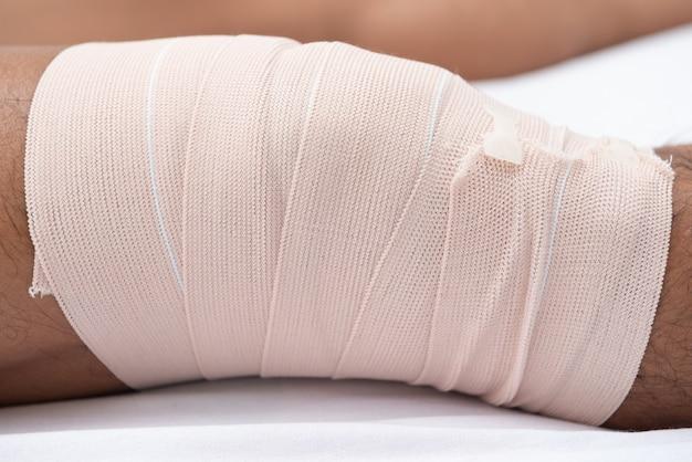 Fisioterapeutas usam as alças na perna do paciente para deitar na cama em uma sala médica.