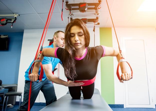Fisioterapia. terapia de treinamento em suspensão. jovem mulher fazendo tração fitness