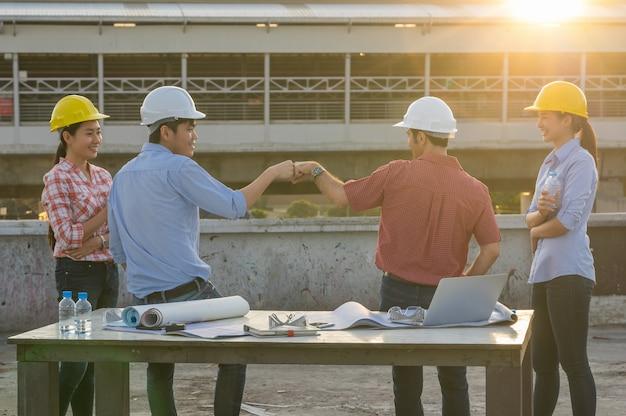 Fist bumping corporate colleagues trabalho em equipe entre engenheiros de construção profissionais