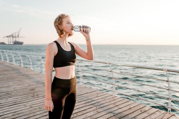 Fit adolescente beber água durante o treino na praia