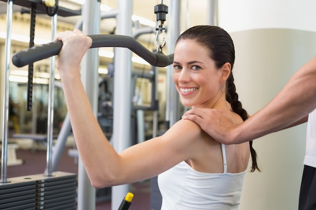 Fit brunette usando pesos máquina para braços com ombros tocando treinador