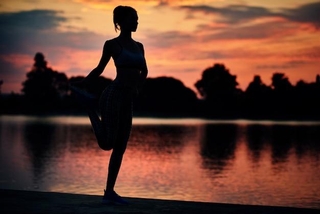 Fit desportista fazendo exercícios de alongamento perto do lago no pôr do sol