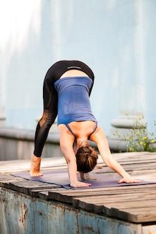 Fit fêmea prática yoga exercício ao ar livre