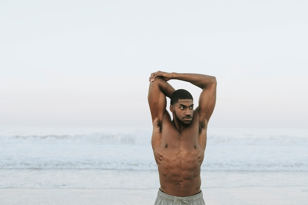 Fit homem alongamento na praia