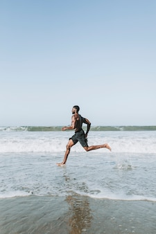 Fit homem correndo na praia