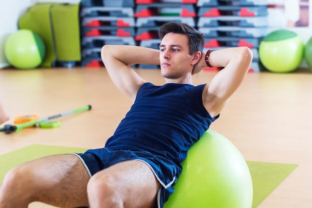 Fit homem fazendo abdominais nas bolas de exercício.