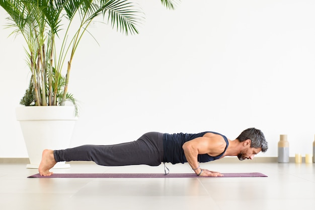 Fit homem fazendo flexões de chaturanga yoga