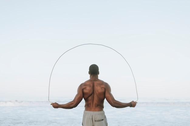 Fit homem pulando corda na praia
