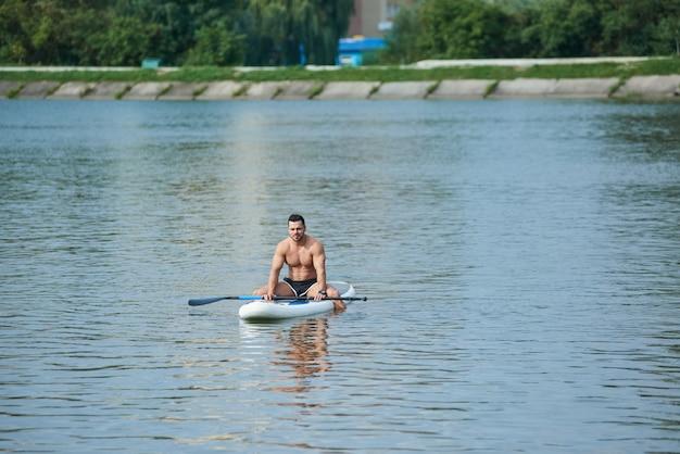 Fit homem relaxando, sentado no sup board, nadando no meio do lago da cidade.