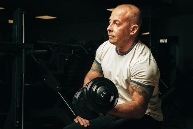 Fit homem sênior exercitar com halteres em uma academia