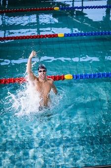 Fit homem triunfando com punho na piscina