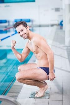 Fit homem triunfando na escala de ponderação na piscina