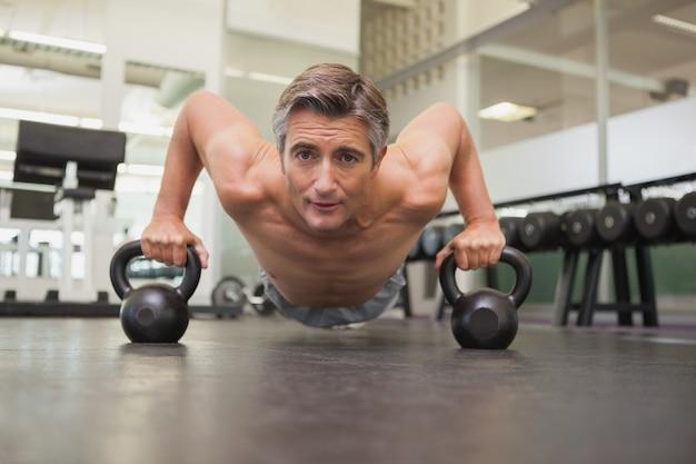Fit homem usando kettlebells em seu treino