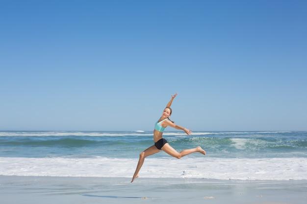 Fit mulher pulando graciosamente na praia