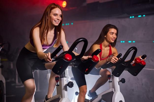 Fit mulheres malhando na bicicleta ergométrica na academia, treino cardio intenso na academia. conceito de esporte e estilo de vida saudável