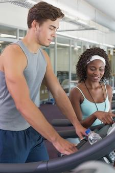 Fit woman on treadmill conversando com personal trainer