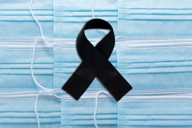 Fita adesiva preta em máscaras médicas. símbolo de luto e morte de luto pelos mortos pelo coronavírus covid-19. fundo de luto