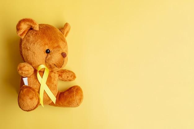 Fita amarela com boneca urso em fundo de cor amarela para apoiar a vida de criança e a doença. setembro mês de conscientização do câncer infantil e conceito do dia mundial do câncer