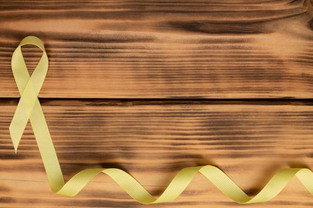 Fita amarela da consciência, sobre fundo de madeira. sarcoma. câncer infantil. dia mundial do câncer. postura plana.