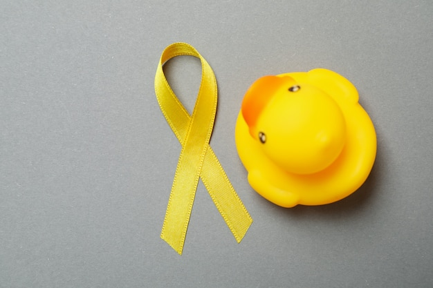 Fita amarela de alerta e pato de borracha em fundo cinza
