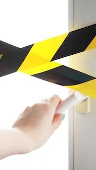 Fita amarela do coronavírus fique em casa. uma mão alcança a maçaneta da porta para abrir a porta e sair. perigo de infecção. quarentena