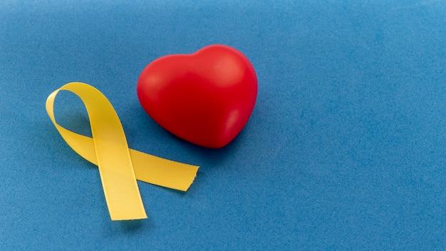Fita amarela e coração vermelho sobre fundo azul. campanha de prevenção ao suicídio. valorizando a vida