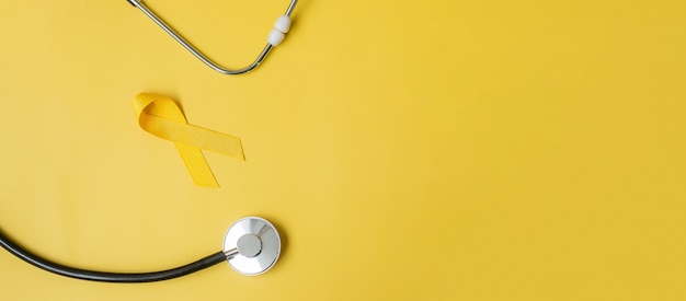 Fita amarela e estetoscópio em fundo amarelo para apoiar as pessoas que vivem e adoecem. setembro dia da prevenção do suicídio, mês da conscientização do câncer infantil e conceito do dia mundial do câncer