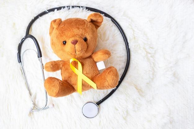 Fita amarela na boneca urso com estetoscópio sobre fundo branco para apoiar a vida de criança e a doença. setembro mês de conscientização do câncer infantil e conceito do dia mundial do câncer