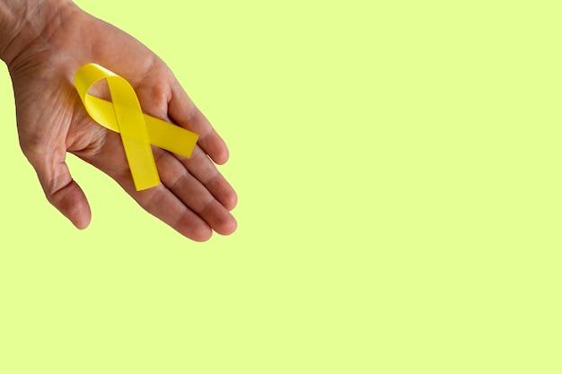 Fita amarela na palma da mão. campanha de prevenção do suicídio. amarelo de setembro.