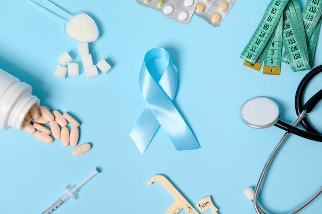 Fita azul de conscientização sobre diabetes no centro de fundo colorido com pílulas farmacêuticas espalhadas, bolhas de comprimidos, seringa de insulina, estetoscópio, compasso de calibre, fita métrica e açúcar branco refinado