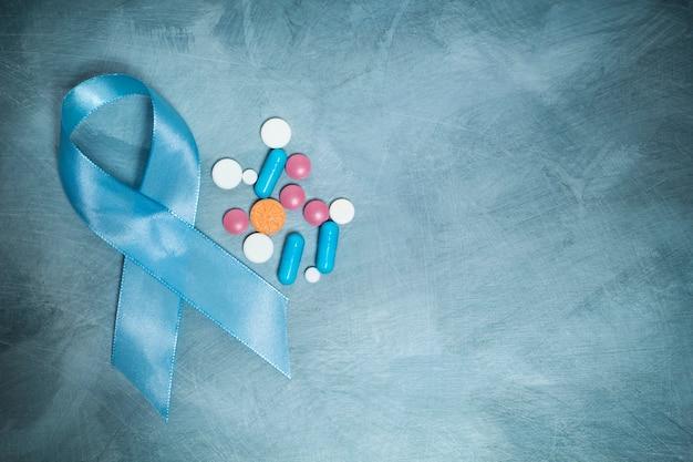Fita azul e comprimidos, um símbolo do câncer de próstata. copie o espaço.