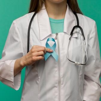 Fita azul para campanha de conscientização do câncer de próstata e conceito de saúde masculina com laço simbólico na mão do médico